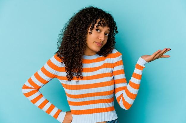 Jeune femme afro-américaine afro-américaine doutant et haussant les épaules dans un geste de questionnement.