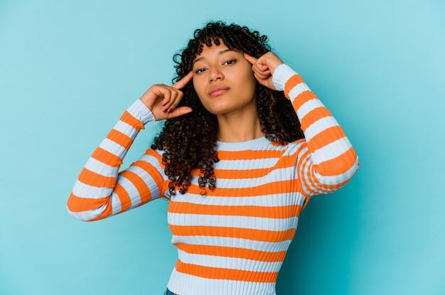 Jeune femme afro-américaine afro-américaine isolée concentrée sur une tâche, gardant l'index pointant la tête.
