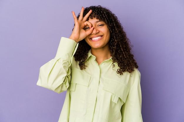 Jeune femme afro-américaine afro-américaine isolée excitée en gardant le geste ok sur les yeux.