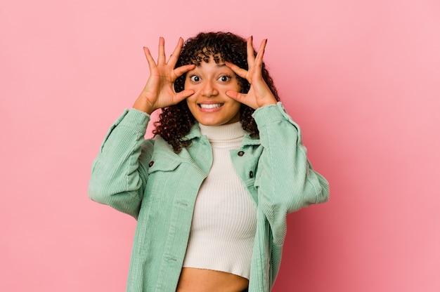 Jeune femme afro-américaine afro-américaine isolée en gardant les yeux ouverts pour trouver une opportunité de succès.