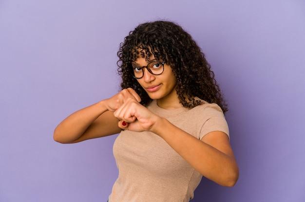 Jeune femme afro-américaine afro-américaine isolée jetant un coup de poing, la colère, les combats en raison d'une dispute, la boxe.