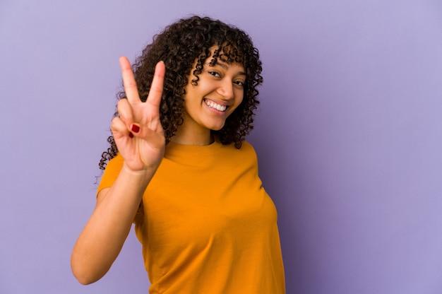 Jeune femme afro-américaine afro-américaine isolée joyeuse et insouciante montrant un symbole de paix avec les doigts.