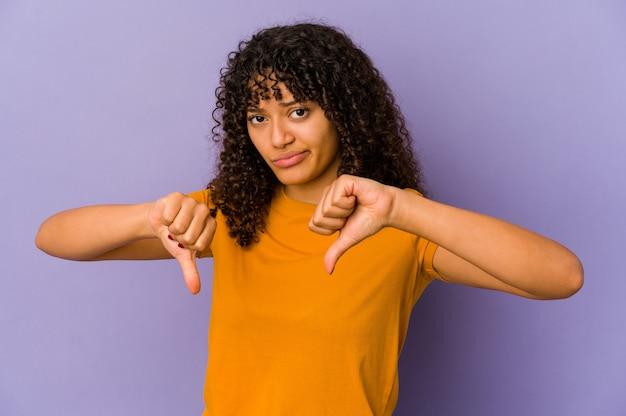 Jeune femme afro-américaine afro-américaine isolée montrant le pouce vers le bas, concept de déception.