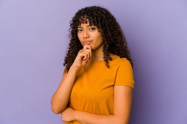 Jeune femme afro-américaine afro-américaine isolée pensant et levant les yeux, réfléchissant, contemplant, ayant un fantasme.