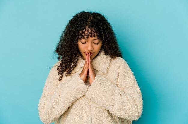 Jeune femme afro-américaine afro-américaine isolée priant, montrant la dévotion, personne religieuse à la recherche d'inspiration divine.