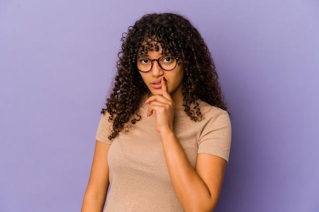 Jeune femme afro-américaine afro-américaine isolée à la recherche de côté avec une expression douteuse et sceptique.