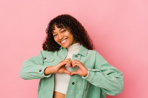 Jeune femme afro-américaine afro-américaine isolée souriant et montrant une forme de coeur avec les mains.