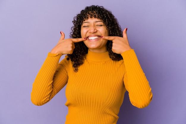 Jeune femme afro-américaine afro-américaine isolée sourit, pointant du doigt la bouche.