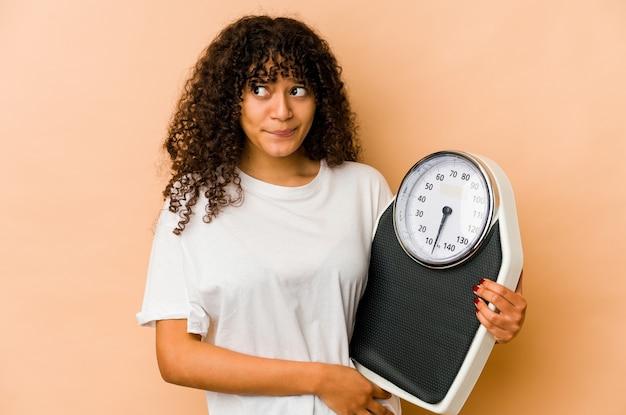 Jeune femme afro-américaine afro-américaine tenant une balance confuse, se sent douteuse et incertaine.