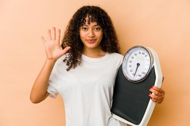 Jeune femme afro-américaine afro-américaine tenant une balance souriant joyeux montrant le numéro cinq avec les doigts.