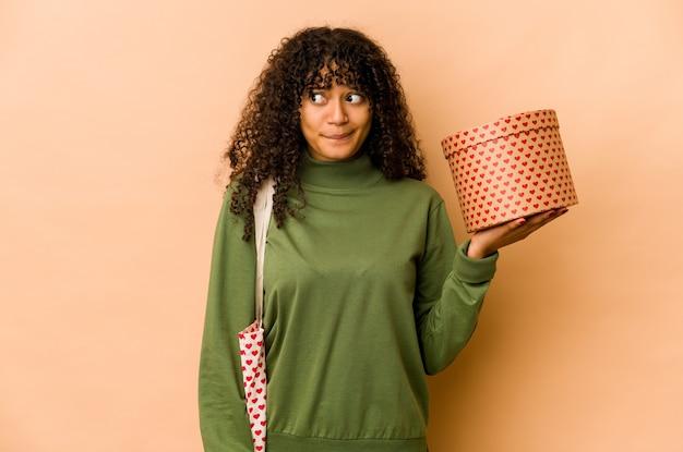 Jeune femme afro-américaine afro-américaine tenant un cadeau de saint valentin confuse, se sent douteuse et incertaine.