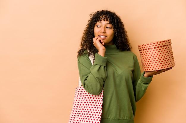 Jeune femme afro-américaine afro-américaine tenant un cadeau de saint valentin détendu penser à quelque chose en regardant un espace de copie.