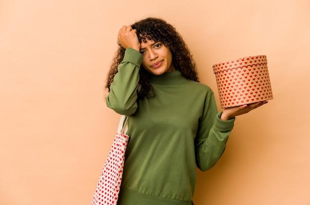 Jeune femme afro-américaine afro-américaine tenant un cadeau de la saint-valentin étant choquée, elle s'est souvenue d'une réunion importante.