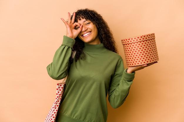 Jeune femme afro-américaine afro-américaine tenant un cadeau de saint valentin excité en gardant le geste ok sur les yeux.