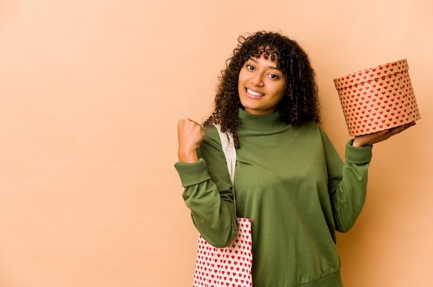 Jeune femme afro-américaine afro-américaine tenant un cadeau de la saint-valentin levant le poing après une victoire, concept gagnant.