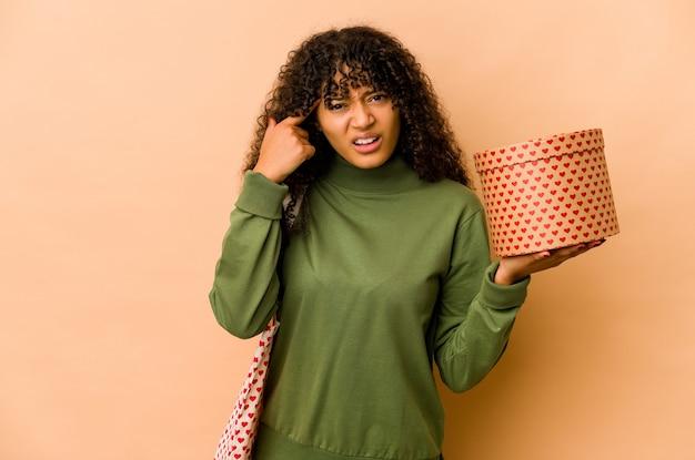 Jeune femme afro-américaine afro-américaine tenant un cadeau de la saint-valentin montrant un geste de déception avec l'index.