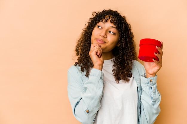 Jeune femme afro-américaine afro-américaine tenant un cadeau de la saint-valentin à la recherche de côté avec une expression douteuse et sceptique.