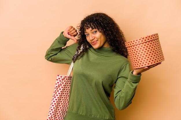 Jeune femme afro-américaine afro-américaine tenant un cadeau de la saint-valentin se sent fière et confiante, exemple à suivre.