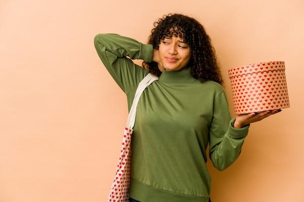 Jeune femme afro-américaine afro-américaine tenant un cadeau de la saint-valentin touchant l'arrière de la tête, en pensant et en faisant un choix.
