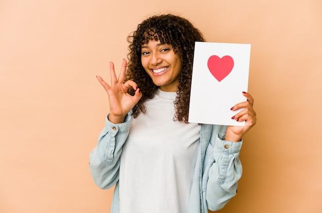 Jeune femme afro-américaine afro-américaine tenant une carte de saint valentin joyeuse et confiante montrant le geste ok.