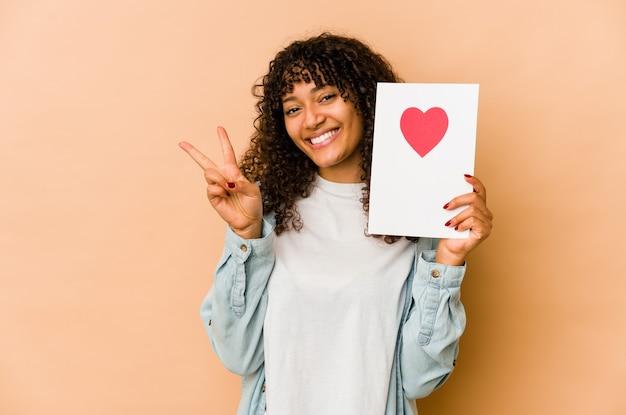 Jeune femme afro-américaine afro-américaine tenant une carte de saint valentin montrant le numéro deux avec les doigts.