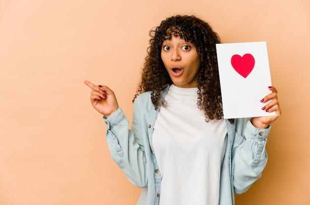 Jeune femme afro-américaine afro-américaine tenant une carte de saint valentin pointant sur le côté