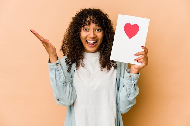 Jeune femme afro-américaine afro-américaine tenant une carte de saint valentin recevant une agréable surprise, excitée et levant les mains.