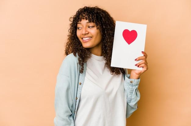 Jeune femme afro-américaine afro-américaine tenant une carte de saint valentin regarde de côté souriant, gai et agréable.