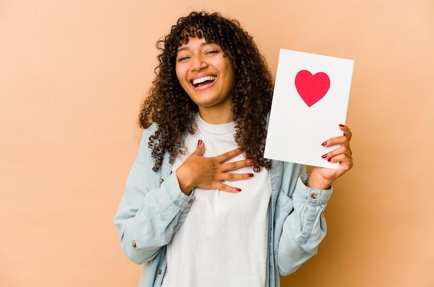 Jeune femme afro-américaine afro-américaine tenant une carte de saint valentin rit bruyamment en gardant la main sur la poitrine.