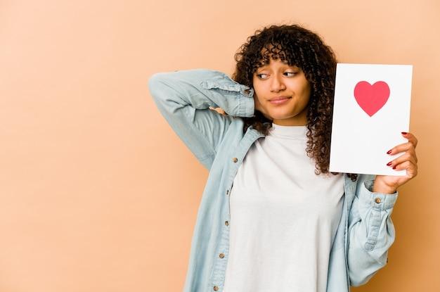 Jeune femme afro-américaine afro-américaine tenant une carte de saint valentin touchant l'arrière de la tête, en pensant et en faisant un choix.