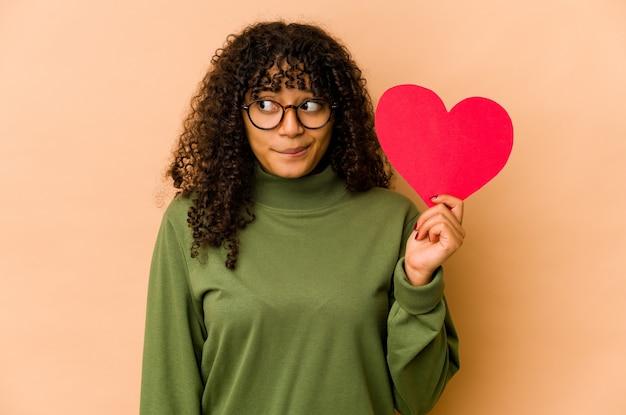 Jeune femme afro-américaine afro-américaine tenant un coeur de saint valentin confus, se sent douteux et incertain.