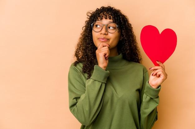 Jeune femme afro-américaine afro-américaine tenant un coeur saint valentin à la recherche sur le côté avec une expression douteuse et sceptique.