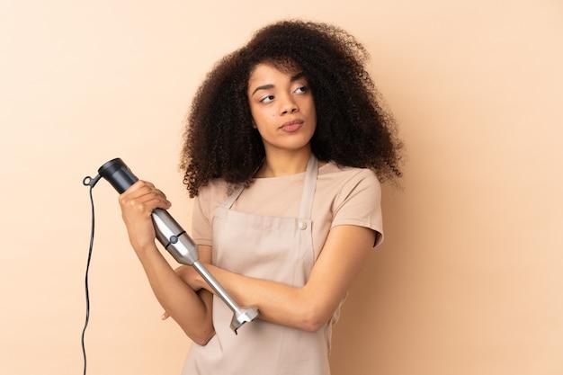 Jeune femme afro-américaine à l'aide d'un mélangeur à main isolé sur un mur beige en pensant à une idée