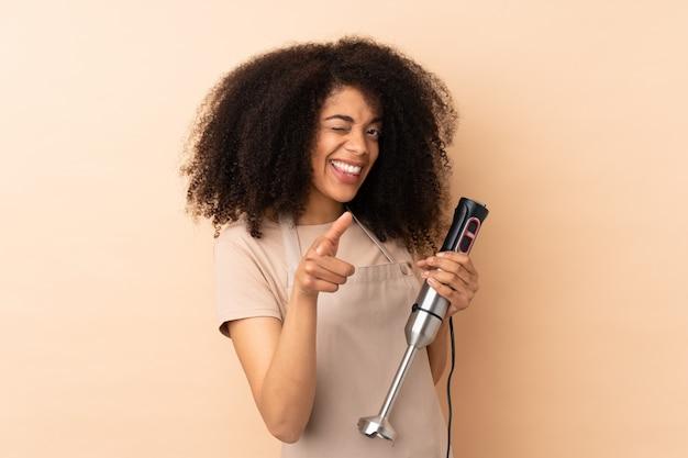 Jeune femme afro-américaine à l'aide d'un mixeur à main isolé sur beige pointe le doigt sur vous