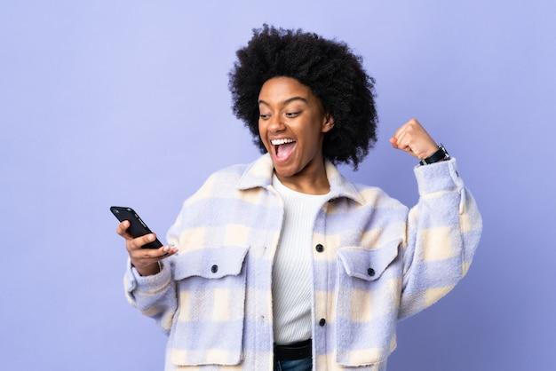 Jeune femme afro-américaine à l'aide de téléphone mobile isolé sur violet célébrant une victoire