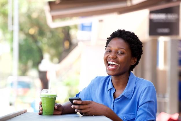 Jeune femme afro-américaine, assise au café en plein air avec un téléphone portable et rire