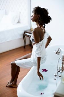 Jeune femme afro-américaine assise sur la baignoire dans la salle de bain