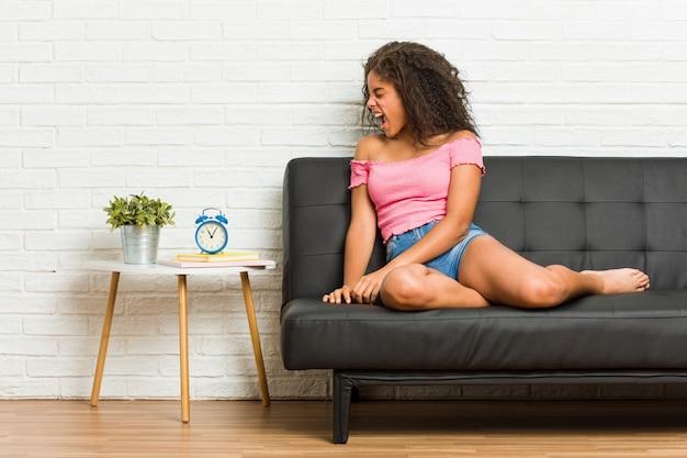 Jeune femme afro-américaine assise sur le canapé en criant vers un espace vide