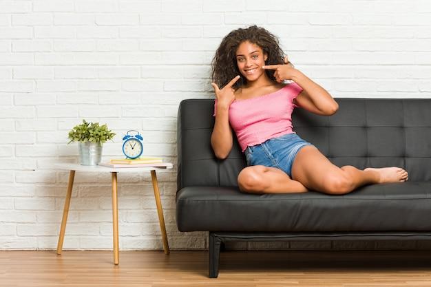 Jeune femme afro-américaine assise sur le canapé sourit, pointer du doigt la bouche.