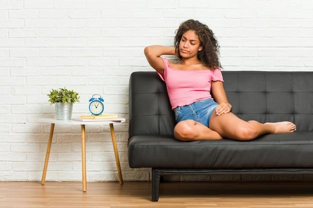 Jeune femme afro-américaine, assise sur le canapé, touchant l'arrière de la tête, pensant et faisant un choix.