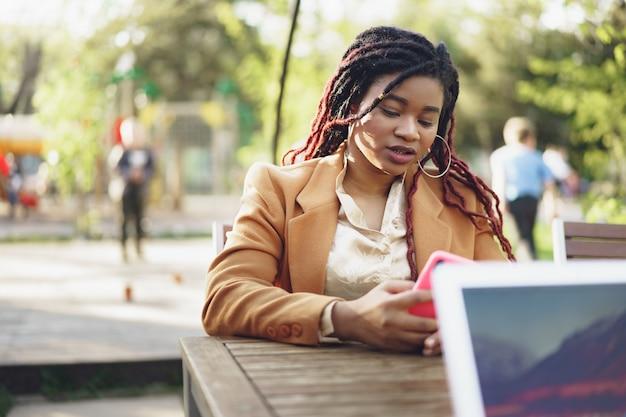 Jeune femme afro-américaine assise dans un café de la rue et tenant un smartphone dans ses mains