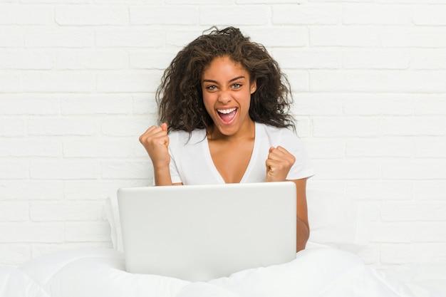 Jeune femme afro-américaine assise sur le lit avec ordinateur portable acclamant sans soucis et excité. concept de victoire.