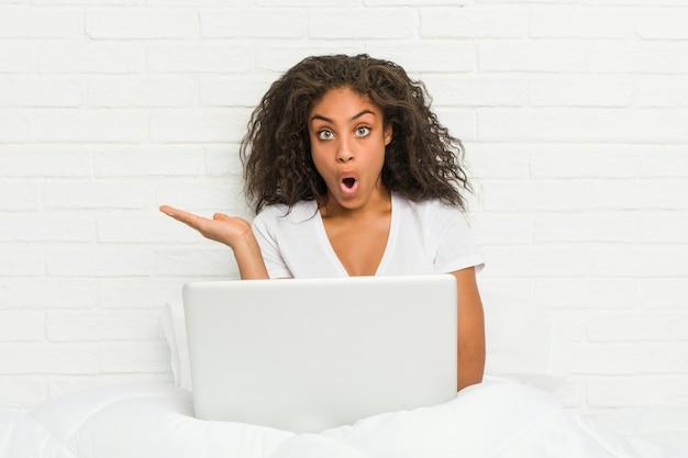 Jeune femme afro-américaine assise sur le lit avec ordinateur portable impressionné tenant copie espace sur la paume.