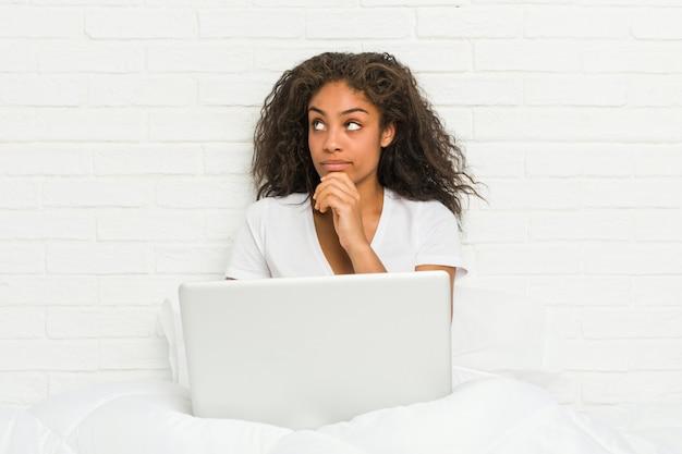 Jeune femme afro-américaine assise sur le lit avec un ordinateur portable à la recherche sur le côté avec une expression douteuse et sceptique.