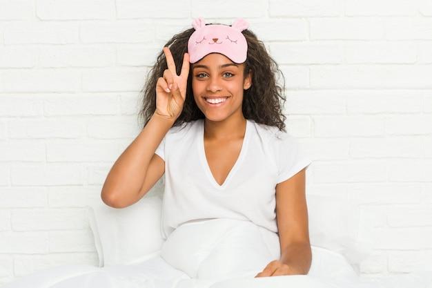 Jeune femme afro-américaine assise sur le lit portant un masque de sommeil montrant le signe de la victoire et souriant largement.