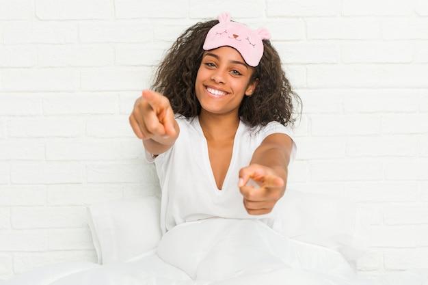 Jeune femme afro-américaine assise sur le lit portant un masque de sommeil, sourires joyeux pointant vers l'avant.