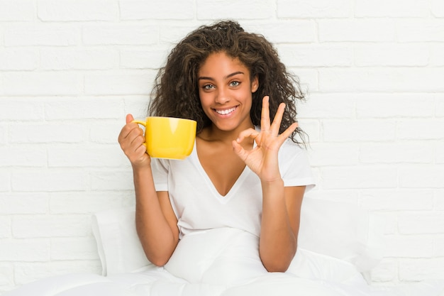 Jeune femme afro-américaine assise sur le lit tenant une tasse de café gaie et confiante montrant le geste ok.