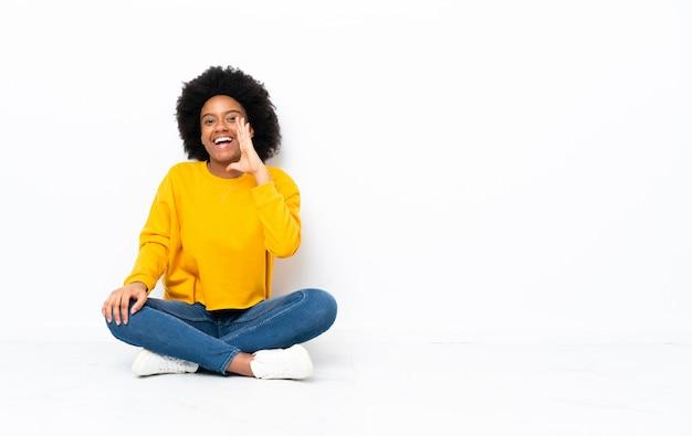 Jeune femme afro-américaine assise sur le sol en criant avec la bouche grande ouverte