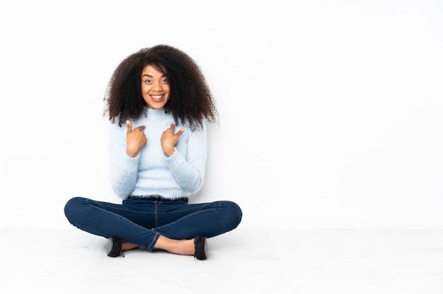Jeune femme afro-américaine assise sur le sol avec une expression faciale surprise