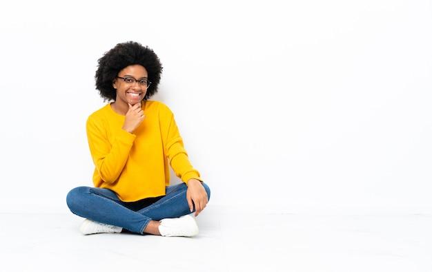 Jeune femme afro-américaine assise sur le sol avec des lunettes et souriant